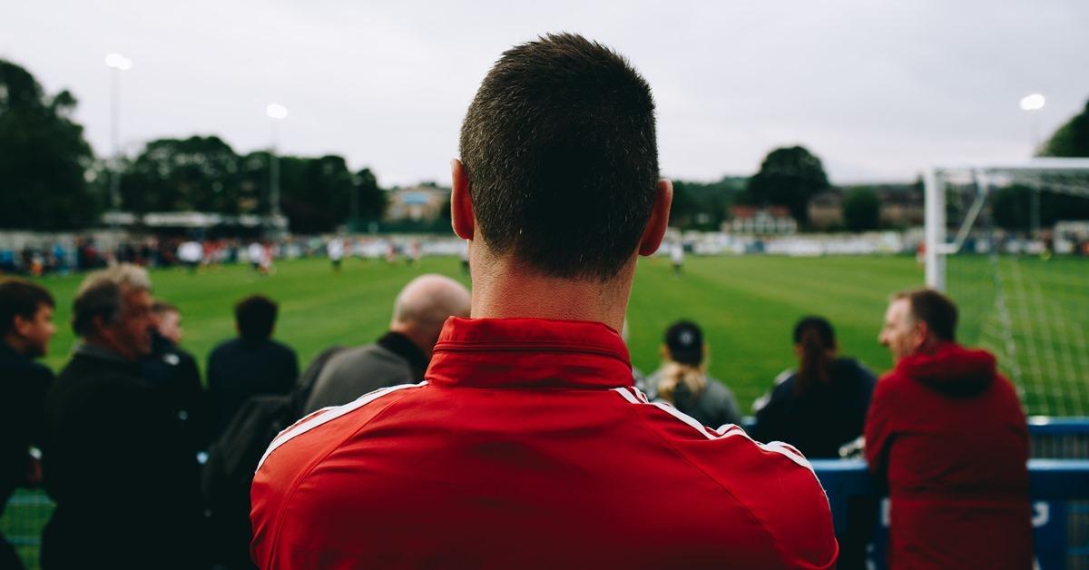 Dečko u crvenom duksu koji gleda fudbalsku utakmicu