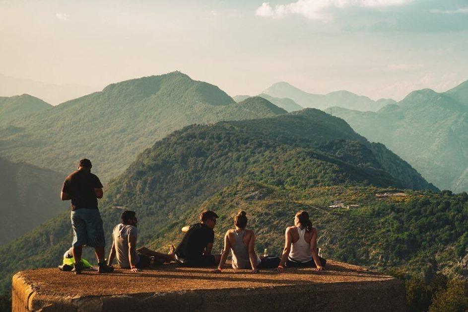 Pogled na brda sa litice na kojoj sede ljudi