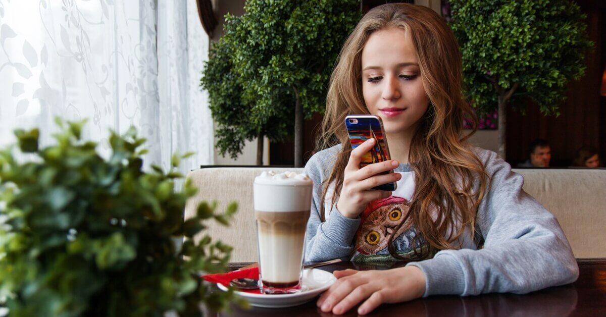 Devojka koja sedi u kafiću i drži mobilni telefon u ruci