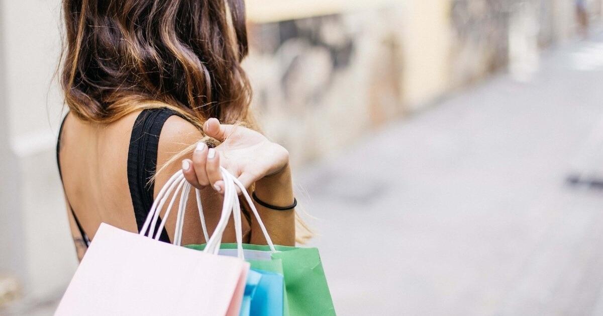 Devojka koja nosi kese iz kupovine na ramenu