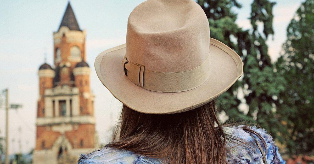 Prikaz šešira na glavi devojke sa crkvom na Gardošu u pozadini