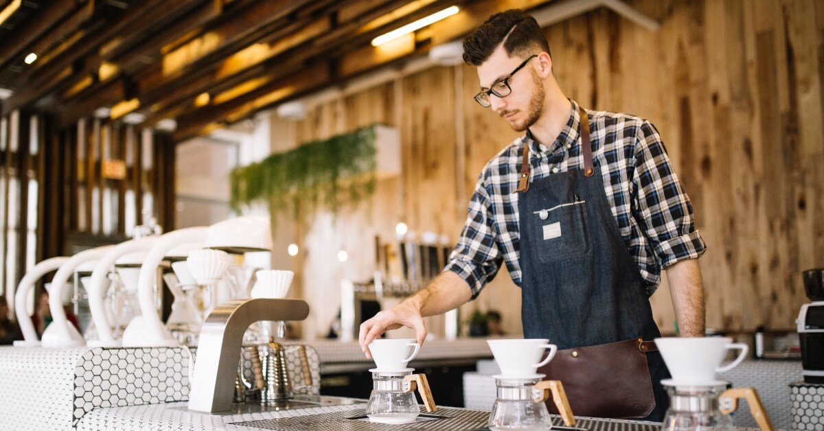 barista u uniformi priprema kafu