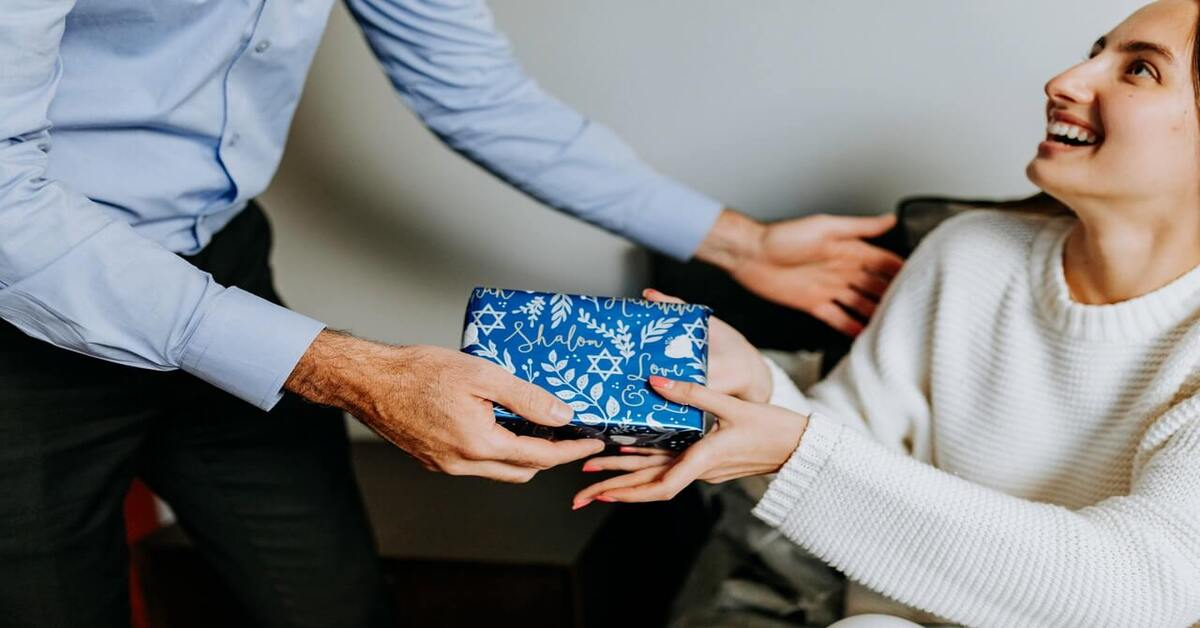 Prikaz darivanja poklona upakovanog u plavi ukrasni papir