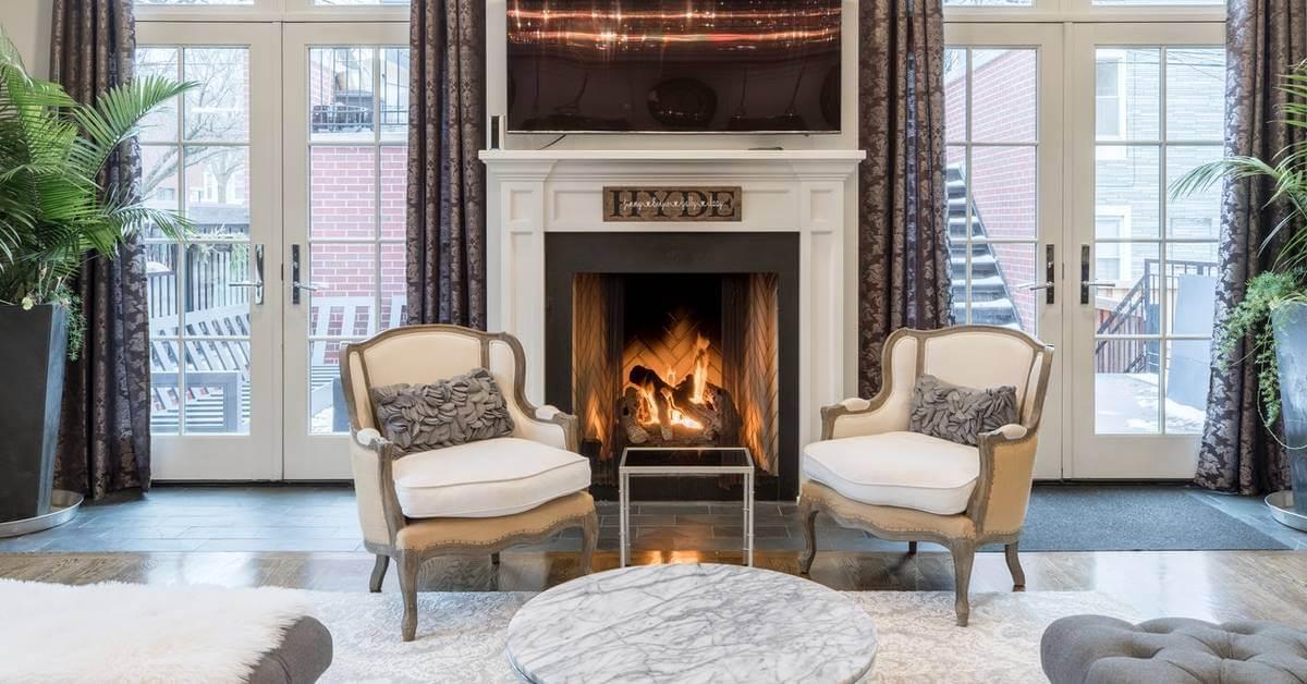 Dve bele luksuzne fotelje i kamin u dnevnom boravku
