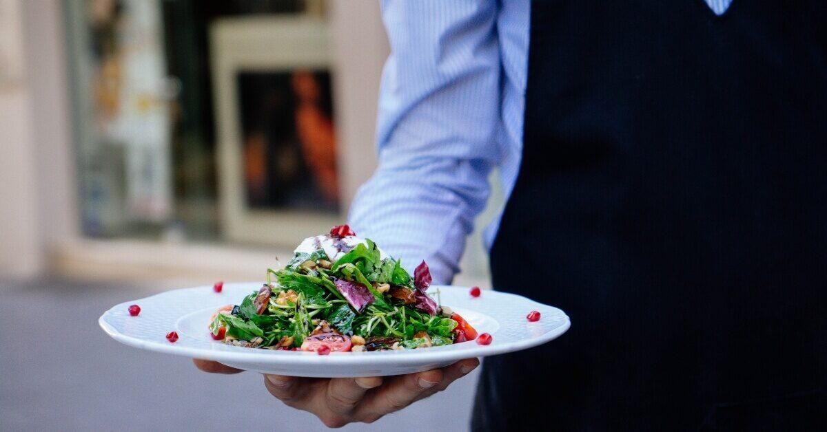 Konobar u uniformi nosi servirano jelo