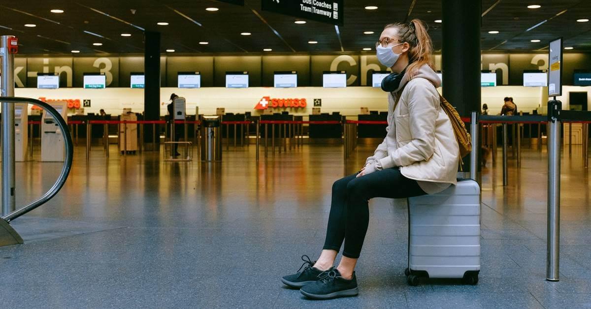 Devojka sa maskom na licu sedi na koferu