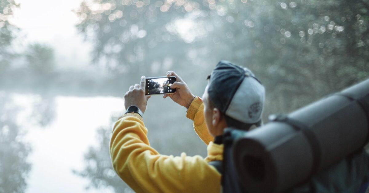 muškarac u žutoj kabanici fotografiše prirodu