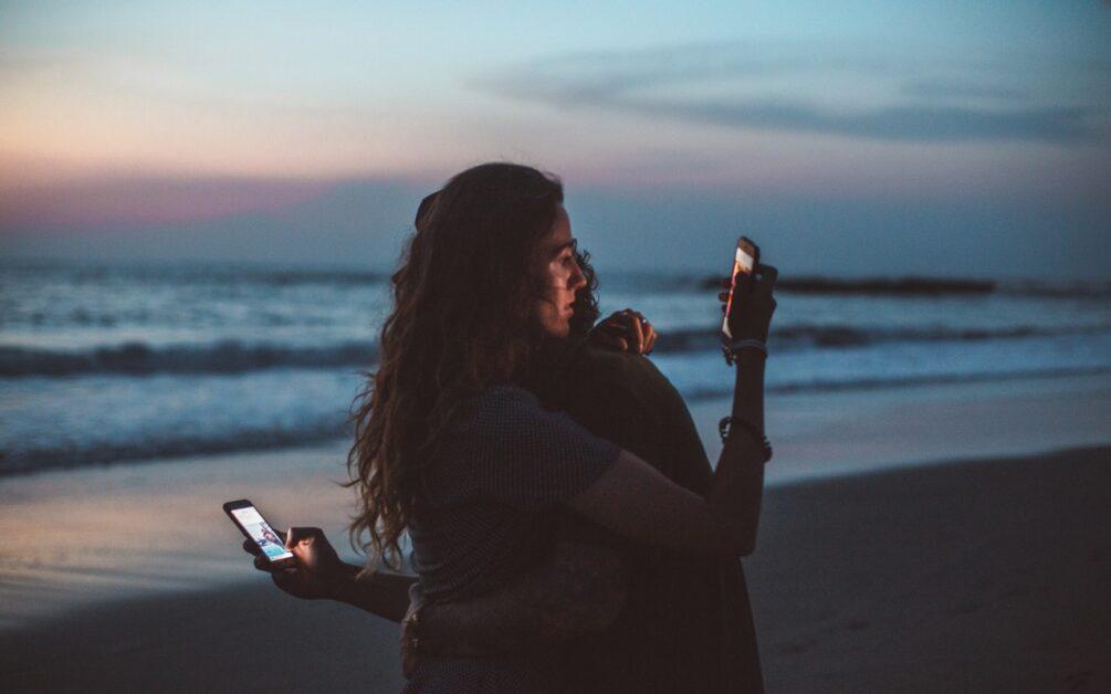 devojka i dečko zagrljeni sa telefonima u ruci na peščanoj plaži